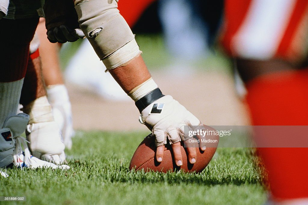 Professional American football, player holding ball on turf : Stock Photo