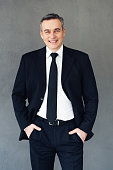 Mature businessman keeping hands in pockets and looking at camera with smile while standing against grey background
