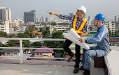 Professional Asian engineering team wearing safety helmet hold blueprint talking about construction project and pointing finger up on the building deck