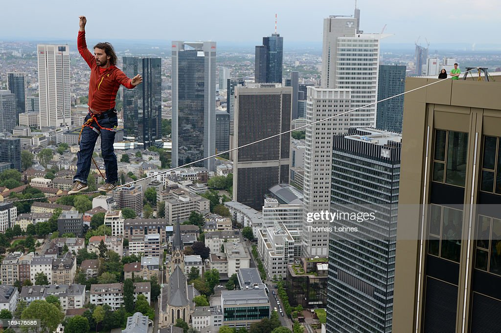 Professional Austrian slackliner Reinhard Kleindl walks along a 30 metre long cable, suspended 185 Meters from the skyscraper PwC on May 25, 2013 in Frankfurt am Main, Germany. It is the highest urban Highline ever, and is part of the Frankfurt Skysraper Festival 2013.