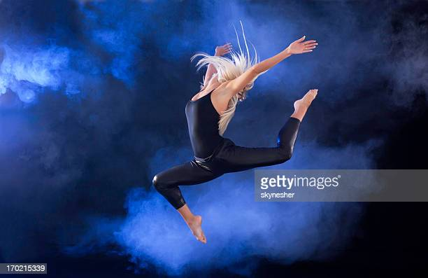 Professional ballerina jumping through the fog.