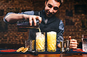 Professional barman preparing cocktails and pouring fresh alcohol in glasses. Cocktails served in bar, restaurant or pub
