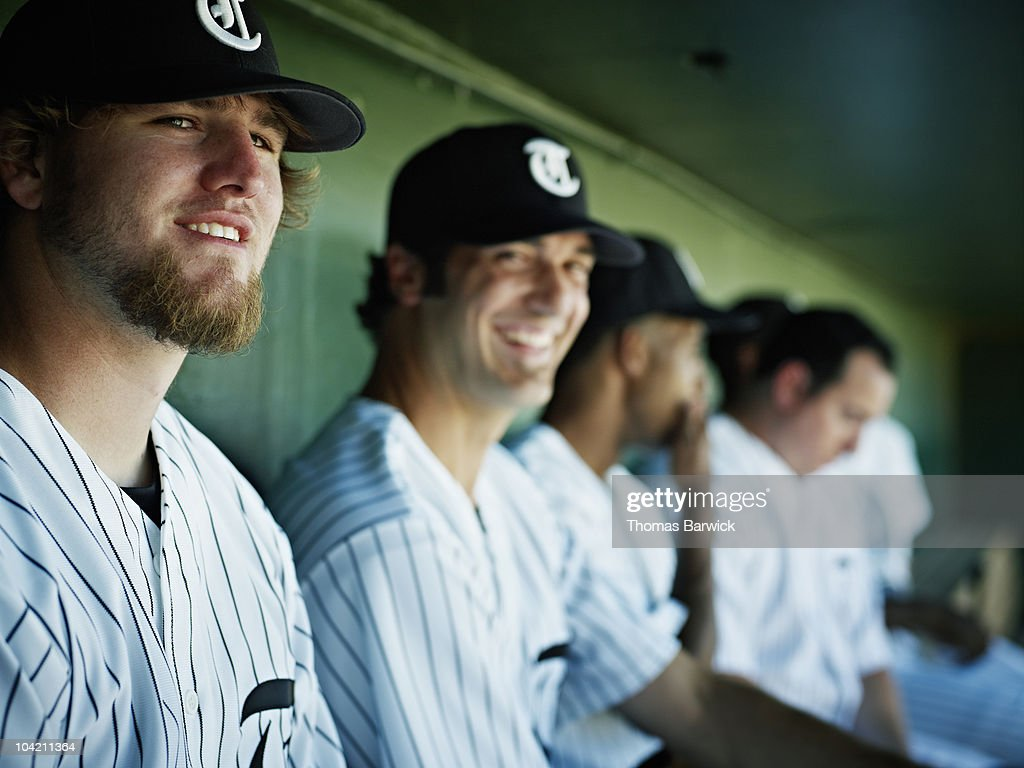 Professional baseball players sitting in dugout : Stock Photo