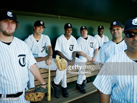 Professional baseball team sitting in dugout : Stock Photo