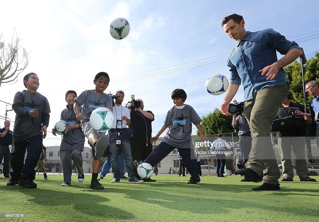Professional basketball player Steve Nash of the Los Angeles Lakers (R) practices a soccer drill with children from The Salvation Army Red Shield Youth & Community Center after announcing his charity soccer events at The Salvation Army Red Shield Youth & Community Center on March 20, 2013 in Los Angeles, California.