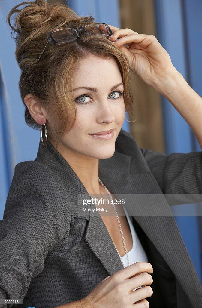 Professional beautiful woman putting glasses on. : Stock Photo