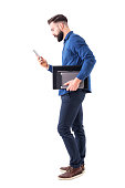 Professional business male executive checking phone carrying tablet and laptop under arm. Side view. Full body isolated on white background.
