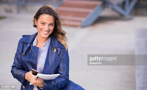 Professional business woman smiling outdoor and holding document