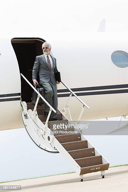 Professional businessman on steps of private jet