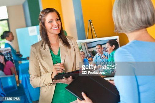 Professional businesswoman using digital tablet interviewing at job fair event