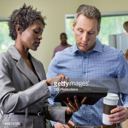 Professional businesswoman using digital tablet to instruct employee : Bildbanksbilder