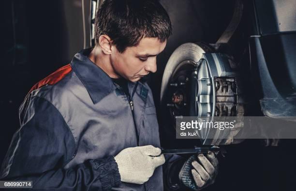 Professional car mechanic repairing brakes