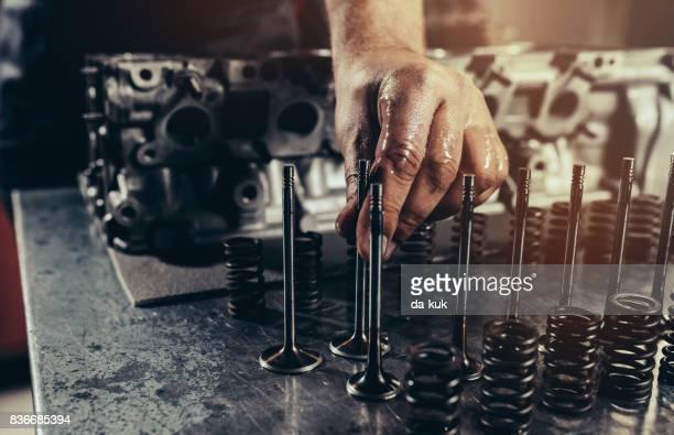 Professional car mechanic repairing V10 engine in auto repair shop