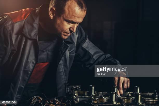 Professional car mechanic repairing V8 engine in auto repair shop