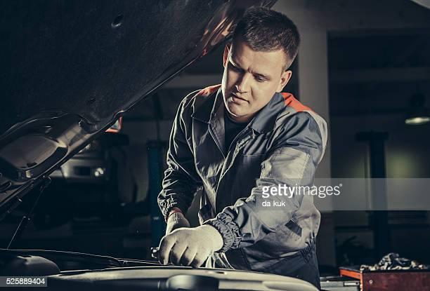 Voiture professionnel mécanicien travaillant dans le service de réparation auto