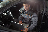 Professional car mechanic working in auto repair service, diagnostic time