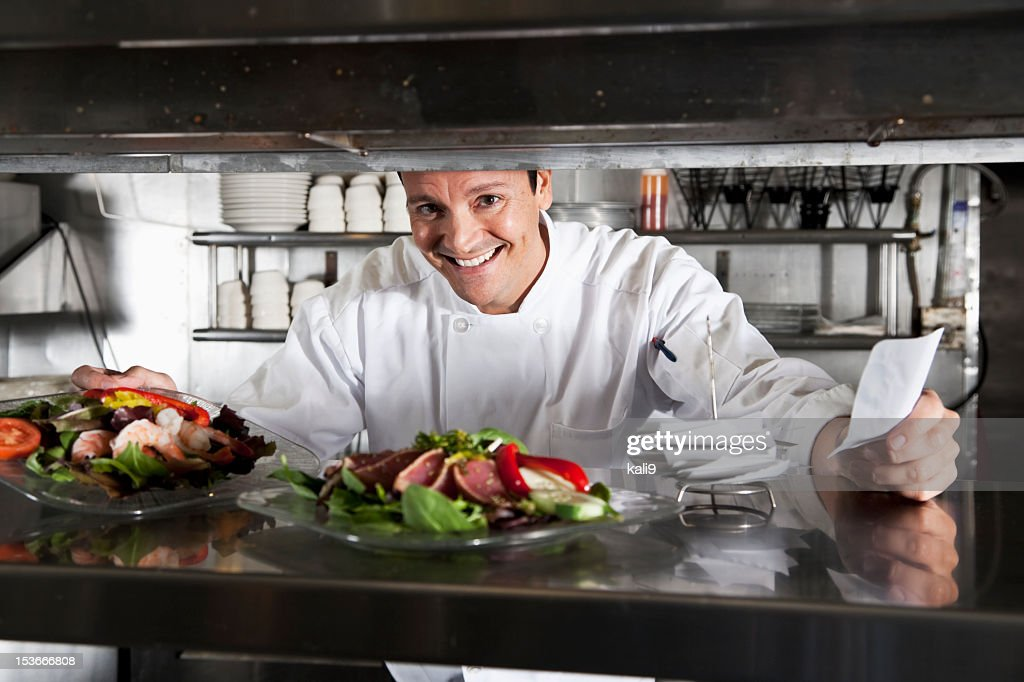 Professional chef in kitchen with customer orders : Stock Photo