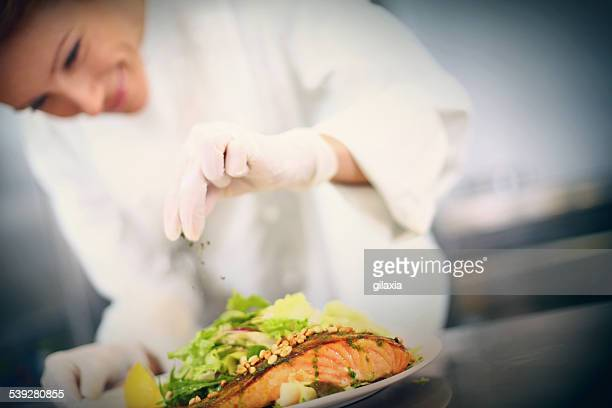 Professional chef places finishing touches on meal