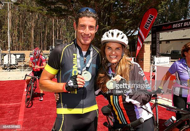 Professional cyclist George Hincapie and Best Buddies Challenge Event CoChair Maria Shriver pose at the finish line of the Best Buddies Challenge...