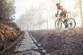 Athlete on bicycle in foggy forest with the sun shining through the trees.