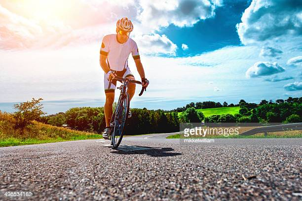 Professional cyclist rides bike with power up a hill