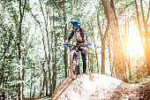 Professional well equipped cyclist standing on the hill while riding downhill in the forest. Concept of an extreme sport and enduro cycling