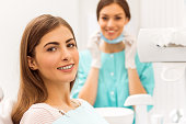 Portrait of a happy patient with braces on the teeth, sitting in the dental chair, in the background a young doctor dentist