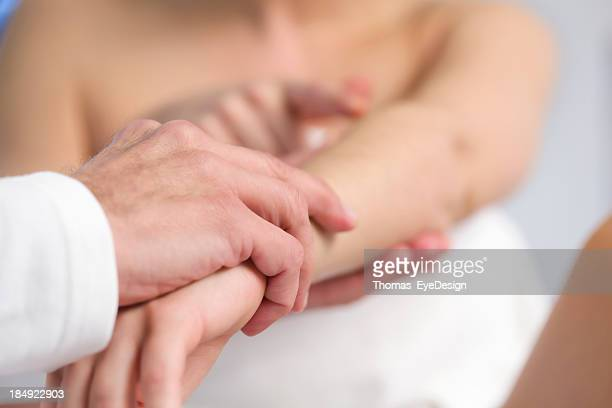 Professional doctor examining arm of a patient.