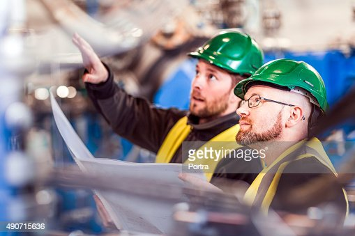 Professional explaining colleague while analyzing machinery in f