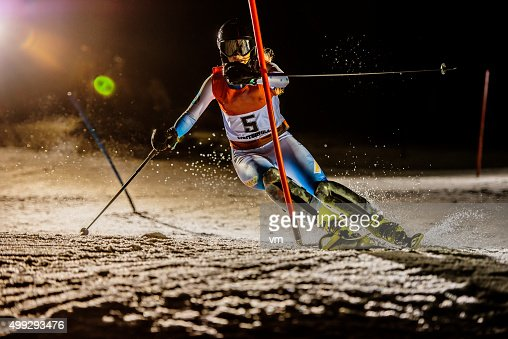 Professional female alpine skiier practicing in the night