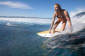 Professional female surfer at Cloud Break Fiji