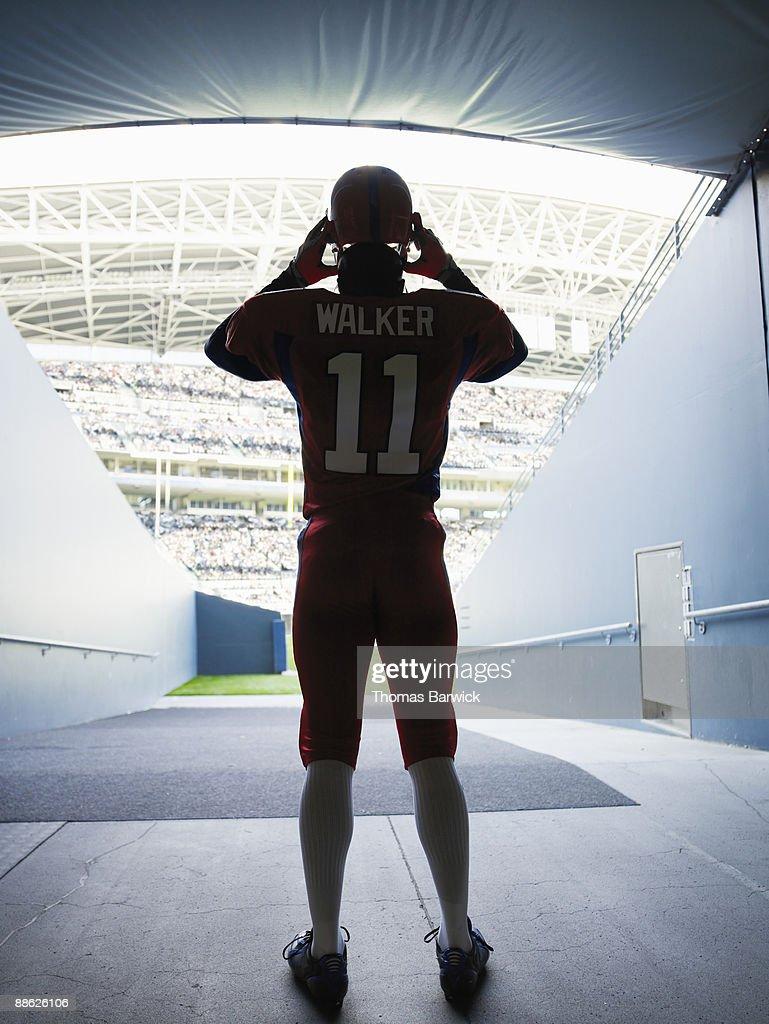 Professional football player putting on helmet