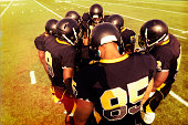 Professional football players huddle on the field.