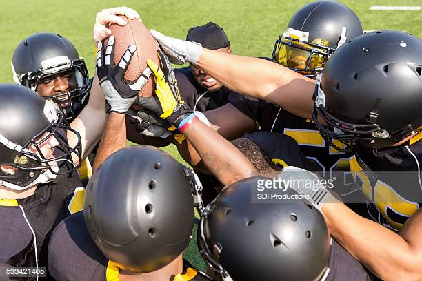 Professional football team in huddle before play on field