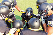 Team of professional or semi-professional adult male American football players are huddled in a circle. They are talking during a time out in game. Players are on the sidelines of green football field