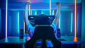 Professional Gamer Playing and Winning in First-Person Shooter Online Video Game on His Personal Computer. Footage Fade out into Bokeh. Room Lit by Neon Lights in Retro Arcade Style. Cyber Sport Champ