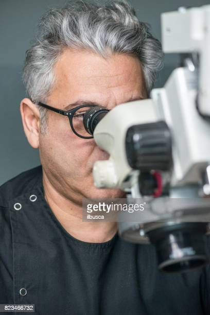 Professional gemstone settings jewellery craft laboratory: man working with microscope