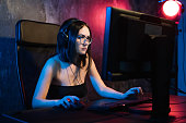 Professional Girl Gamer Plays in MMORPG or Strategy Video Game on Her Computer. She's Participating in Online Cyber Games Tournament, Plays at Home, or in Internet Cafe. She Wears Gaming Headset.