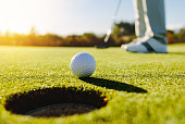 Professional golfer putting ball into the hole. Golf ball by the edge of hole with player in background on a sunny day.