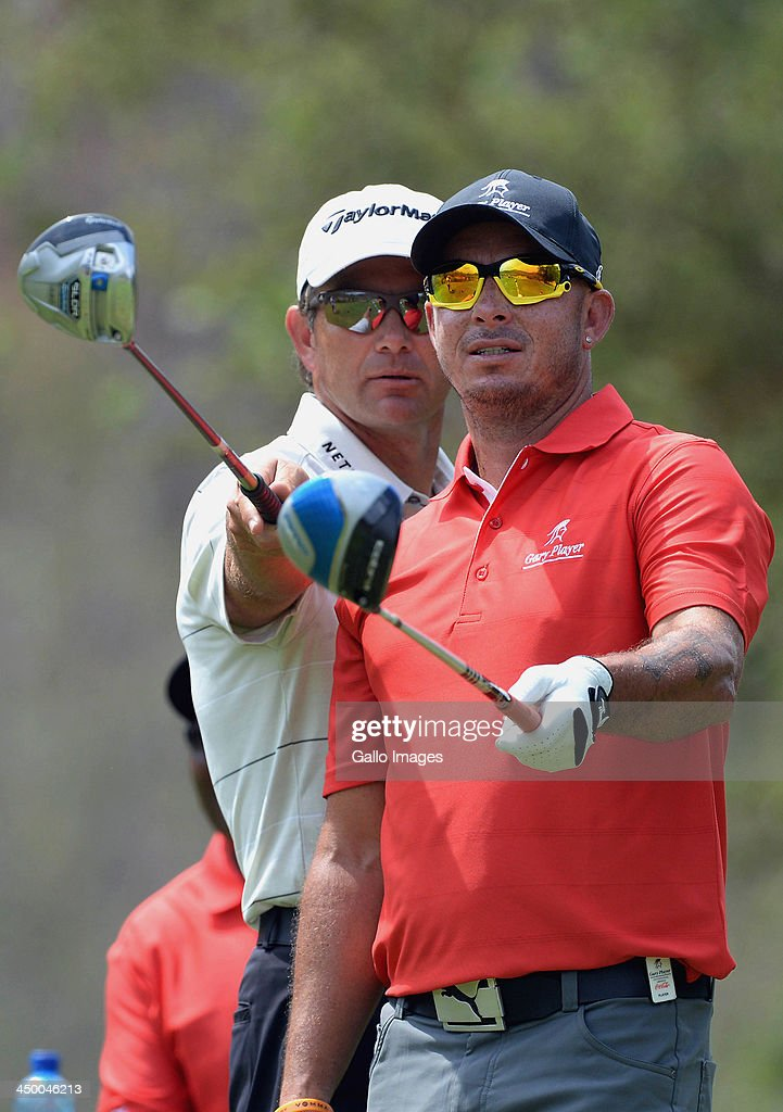Professional Golfer Retief Goosen and Herschelle Gibbs (R) line up a shot during Round 1 of the Gary Player Invitational presented by Coca-Cola at the Lost City Golf Course on November 16, 2013 in Sun City, South Africa.