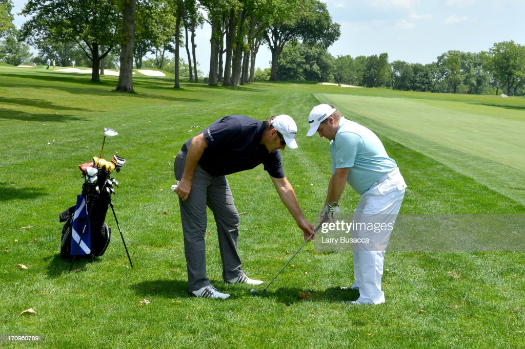 Professional Golfer Sir Nick Faldo (L) instructs Vice President of Glenmorangie Brian Cox during a Gold Day hosted by Glenmorangie and Sir Nick Faldo at Winged Foot Golf Club on June 20, 2013 in Mamaroneck, New York.