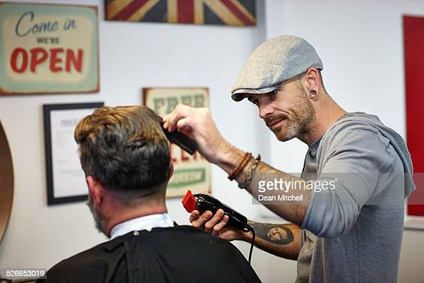 Professional hairdresser cutting man's hair