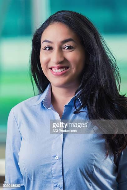 Professional headshot of mid adult Hispanic businesswoman in office