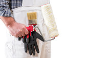 House painter worker with white work overalls, keeps the roller to paint in his hand. Isolated on white background. Text space