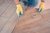 Professional installation of floor covering, the worker quickly and qualitatively mounts a laminate board