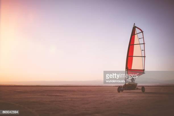 Professionele land yachting atleet beoefenen op het strand bij zonsondergang