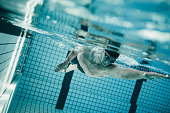 Underwater shot of young sportsman swimming in pool.  Professional male swimmer inside swimming pool.