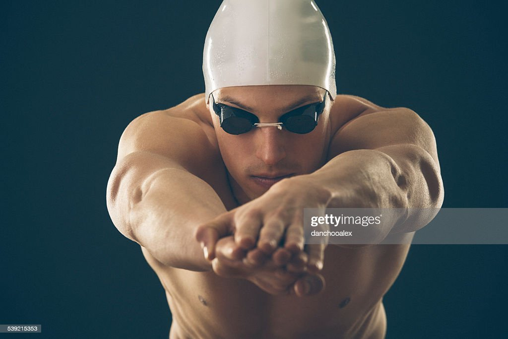 Professional male swimmer preparing for jump : Stock Photo