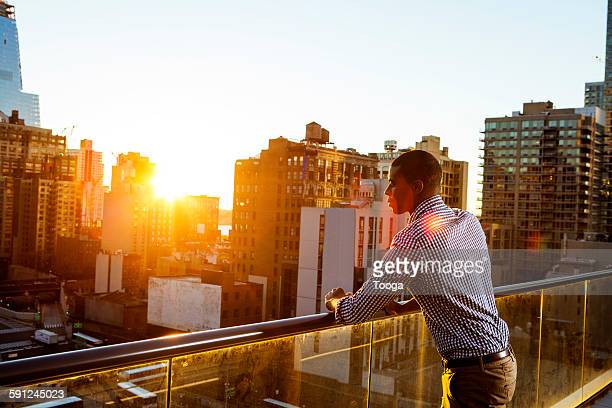 Professional man looking down at bustling city
