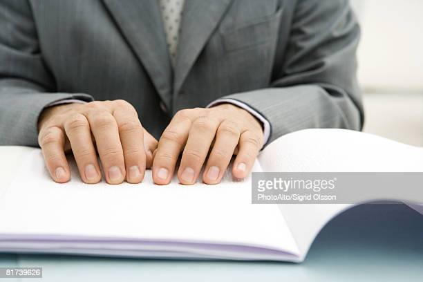 Professional man reading Braille, cropped view of hands